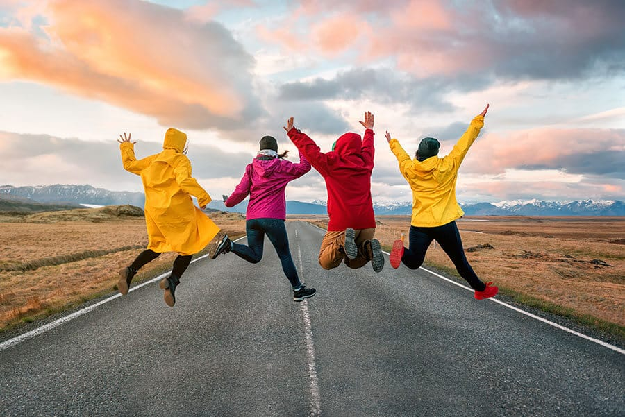 Friends jumping on the road in Iceland