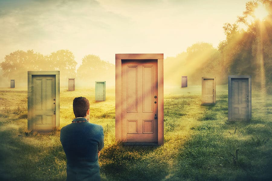 man in front of many different doors