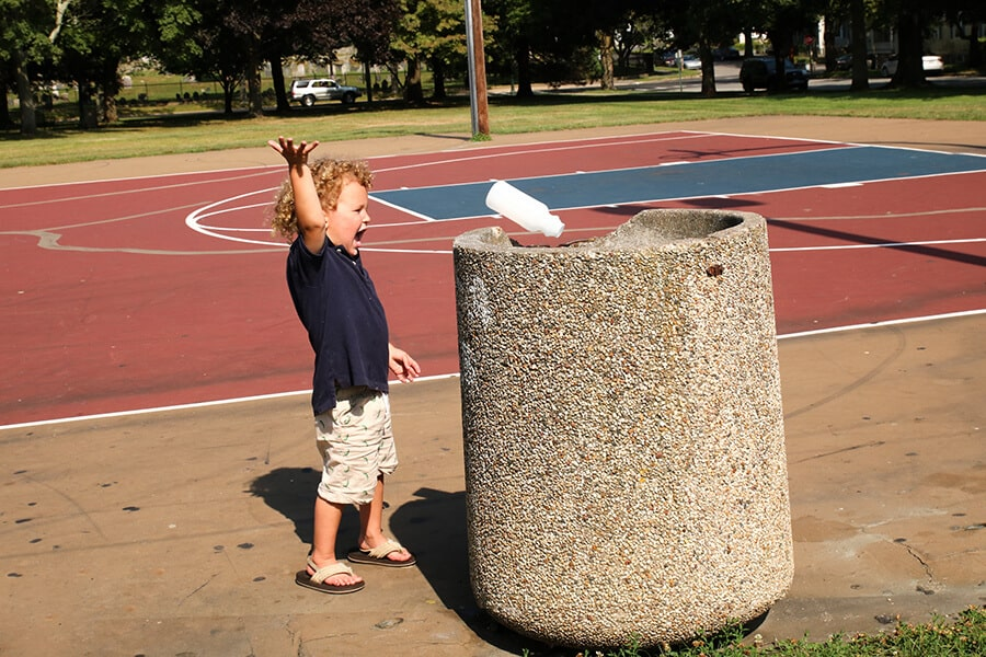 Boy throwing away garbage in a public trash container