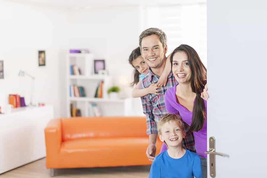 Family standing at front door inviting in