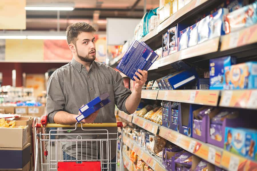 Man confused with the range of goods in supermarket