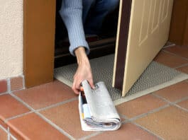 Woman picking up magazine by the door