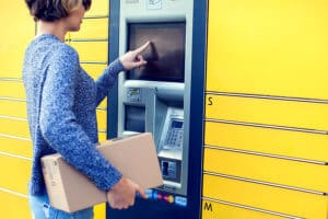 Woman using automated self service locker to deposit the parcel
