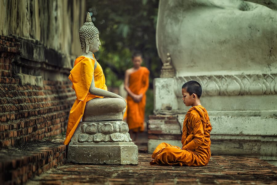 Young Novice monk praying in front of Buddha statue