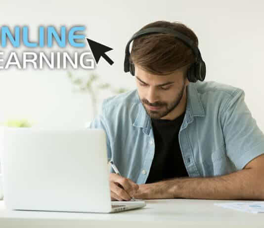 Focused man with headphones writing notes studying an online course