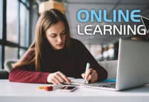 Young student scribing notes while taking an online course