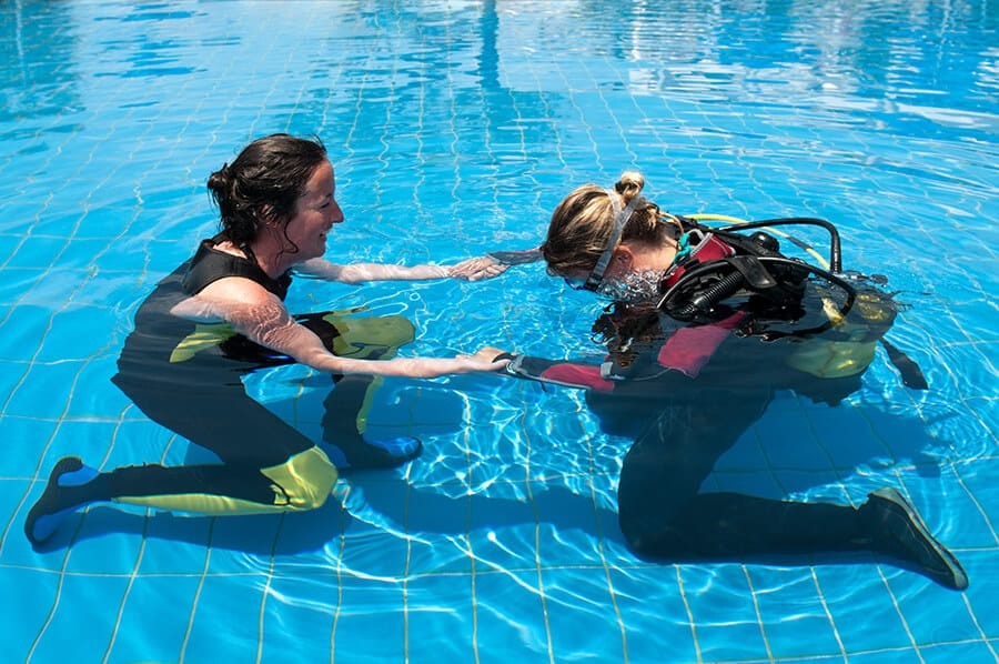 Scuba diving instructor and student in a swimming pool