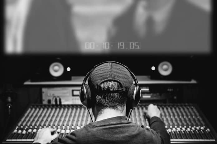 Composer mixing audio track and music score on movie in sound studio