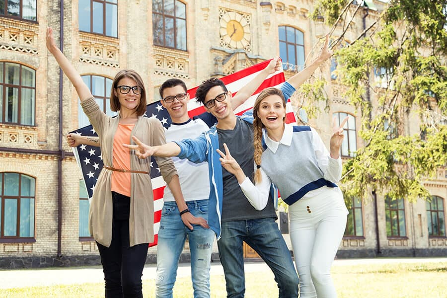 Group of students holding flag of USA on the university campus
