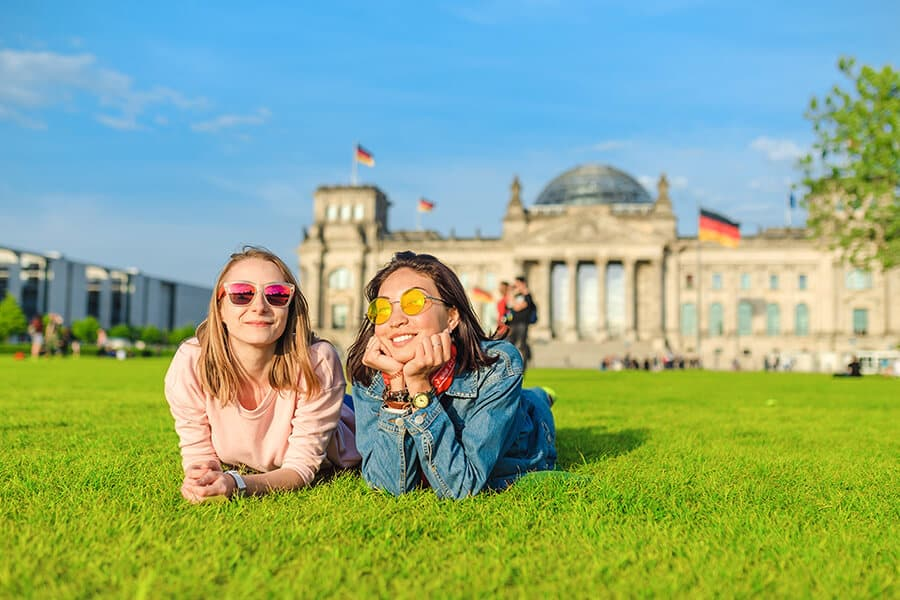 Two students lying on a grass in front of the Bundestag building in Berlin