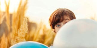 Child behind baloons / Photo: Ramin Talebi on Unsplash