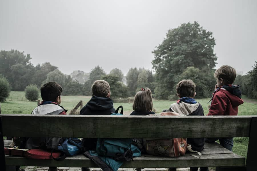 Children sitting on the bench / Photo: Piron Guillaume on Unsplash