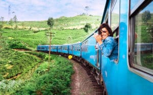 Happy smiling woman enjoying traveling by train on in Sri Lanka