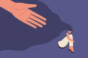 Helping hand towards sad young girl in depression