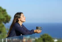 Relaxed woman on her balcony with the ocean view