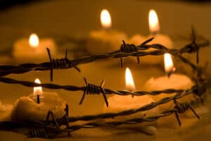 Burning candles in barbed wire symbol of hope and freedom