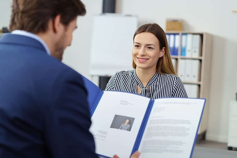 HR reading a CV and cover letter of the interviewed woman